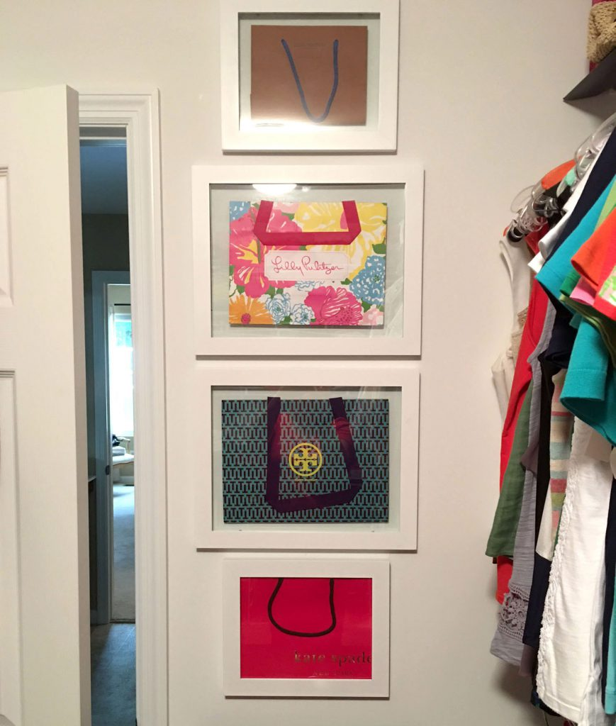 Various shopping bags inside picture frames in a closet.