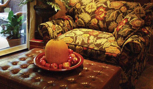 A pumpkin and group of apples resting on a tray that sits on top of an ottoman.