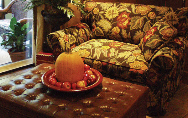 A pumpkin and group of apples resting on a tray that sits on top of an automan.