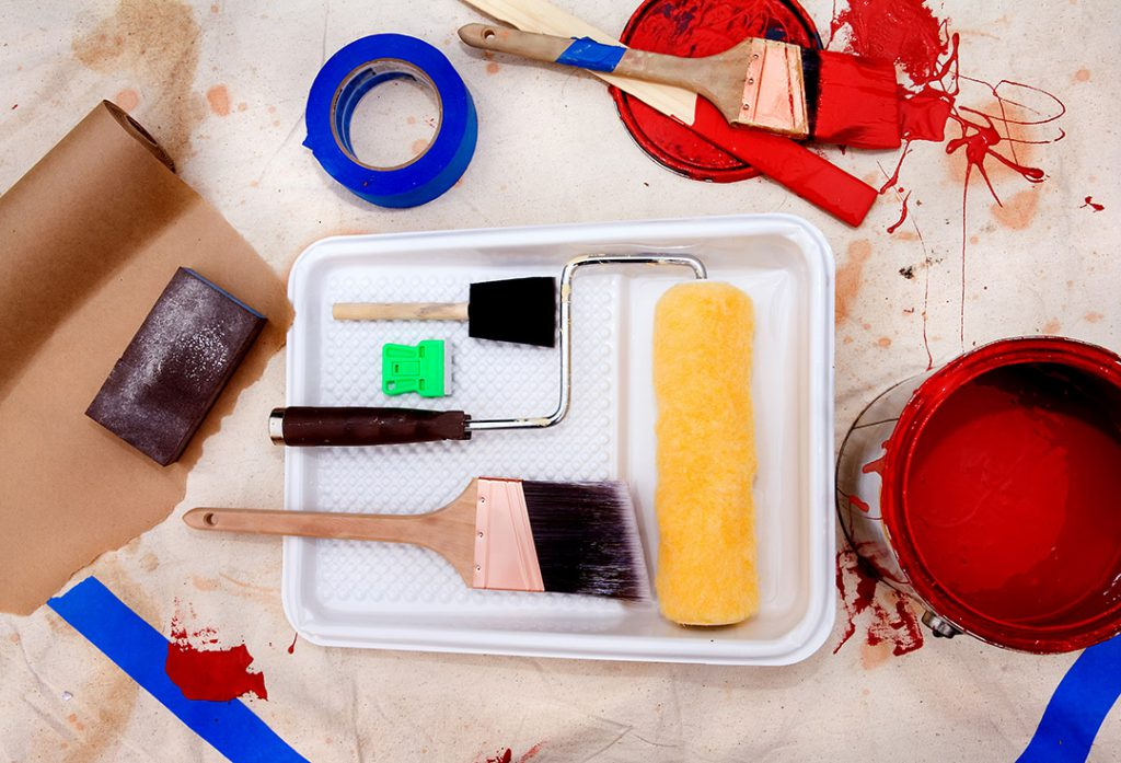 A pile of painting tools on a tarp.