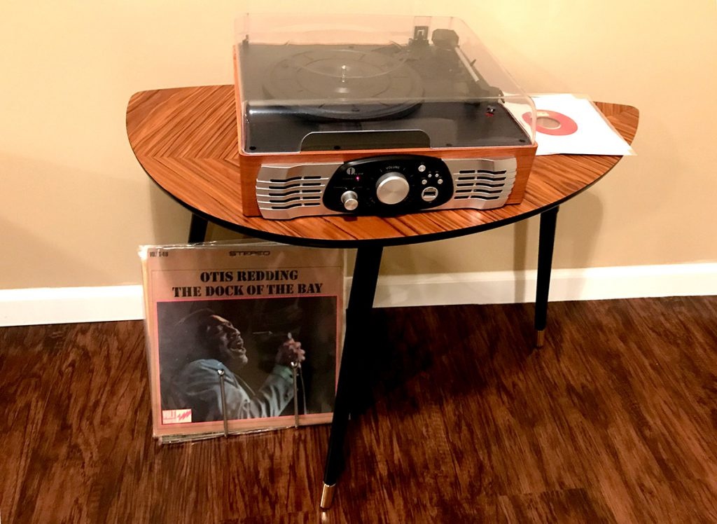 A record player sitting on top of an end-table, with a vinyl record underneath.