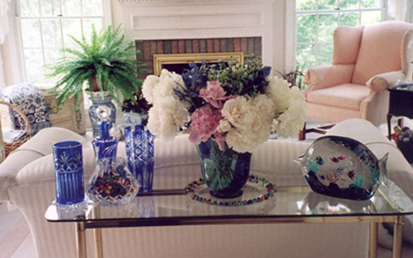 A vase full of flowers with other decorations and a fish tank on top of a glass end table.