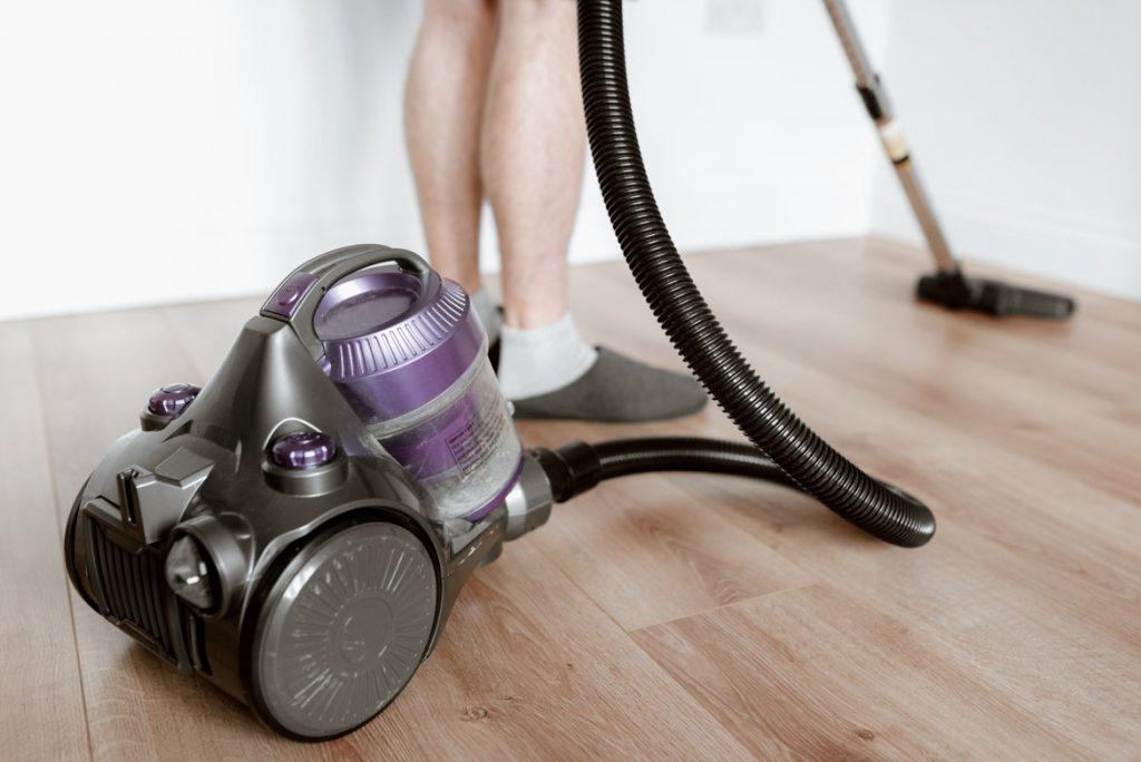 A closeup of a man using a vacuum on a hardwood floor