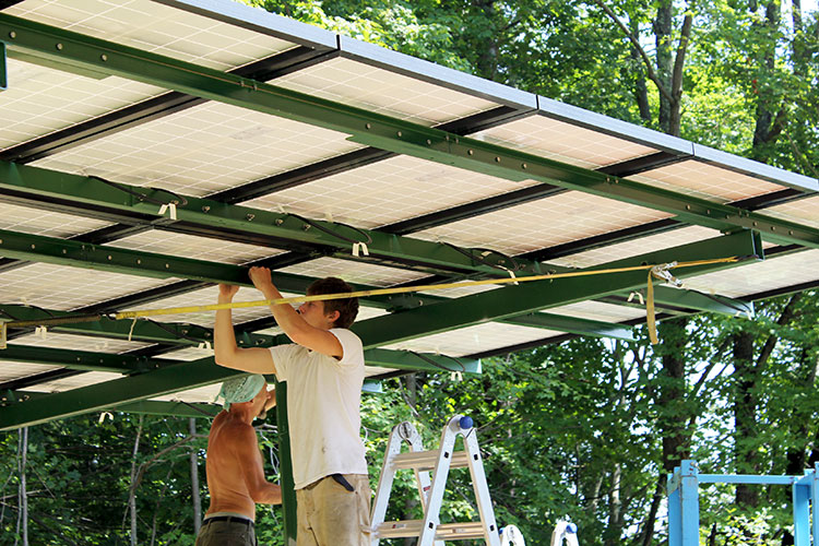 PV installers working underneath a pole mounted array.