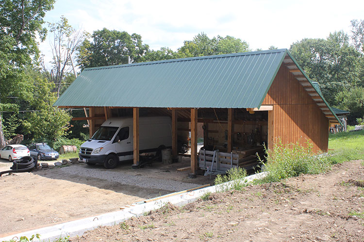 Northwest view of the solar-powered timber frame EV building.