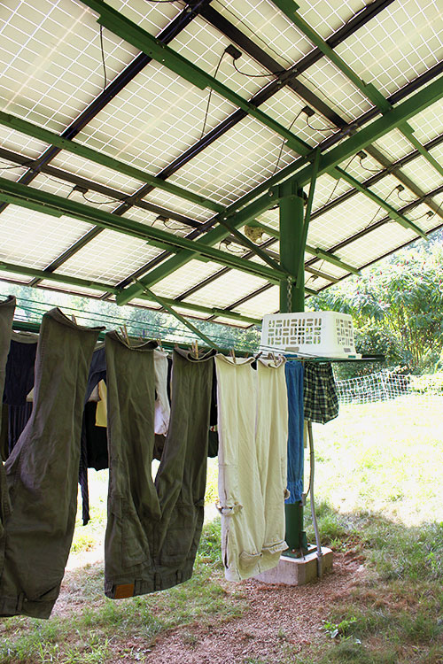 Clothes drying on line underneath solar panels.