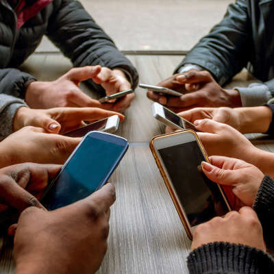 six sets of hands set up in a circle all holding various smartphone models as though they are texting