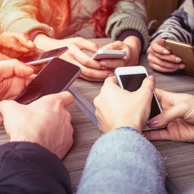 five sets of hands set up in a circle all holding various smartphone models as though they are texting