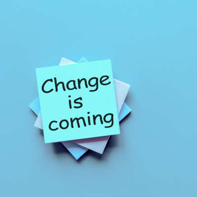 """Light blue background, a stack of sticky note pads at the center, written on the top is """"change is coming"""" in black lettering"""
