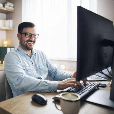 A white male with dark hair, a dark beard, and black framed glasses in a light blue button up shirt sits smiling at his desktop monitor. A black wireless mouse is beside him as well as a coffee mug.