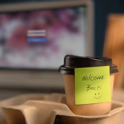 """Tan to-go coffee cup with a black lid sits in a carrier with a green post-it note reading """"welcome back"""""""