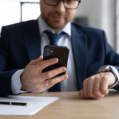A man with dark rimmed glasses and a beard wearing a suit and tie holds a black iphone up looking at it.