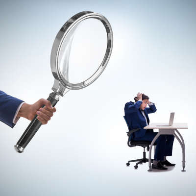 On the left, a hand holds a large magnifying glass over a small man on the right sitting at a deskin front of his laptop with his hands on his head in madness