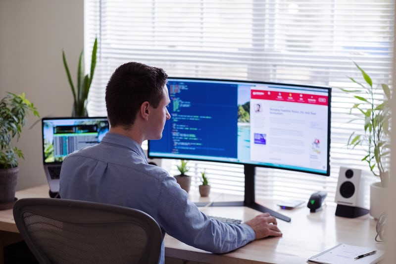 Male in a blut botton down shirt works on various monitors at a desk, surrounded by plants
