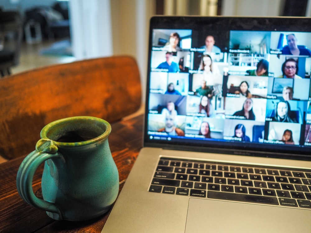 Laptop on a table next to a cup of coffee with the screen showing a large number of people on a video conference call