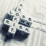 """Word dice spell """"profit,"""" """"loss,"""" & """"risk"""" on top of a stock paper."""