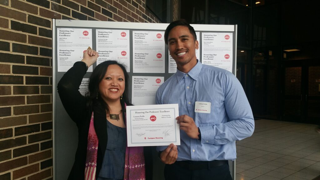 Two professors pose with a certificate for teaching