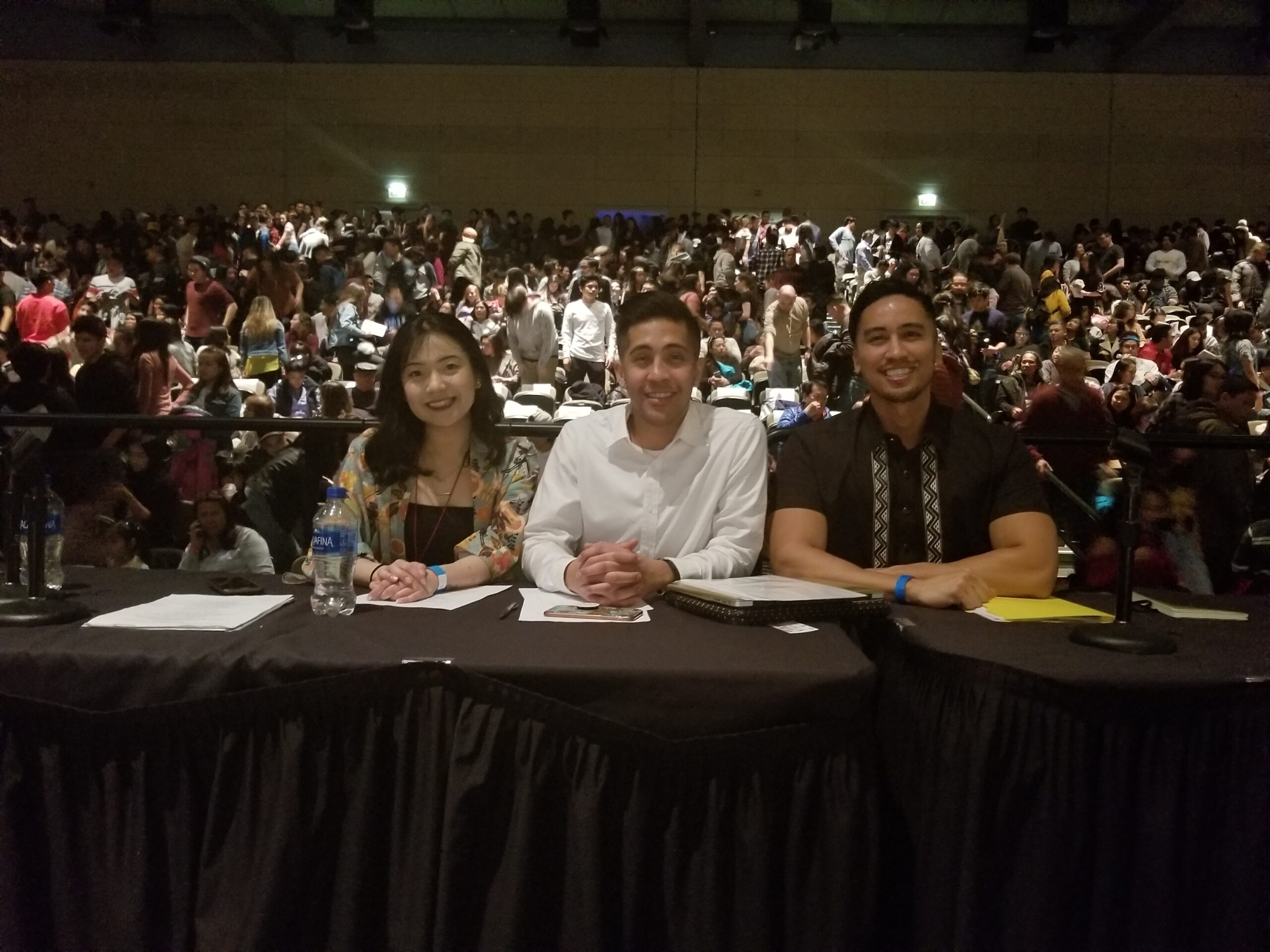 Three Filipino judges, one woman and two men, sit at a table in front of a large seated audience