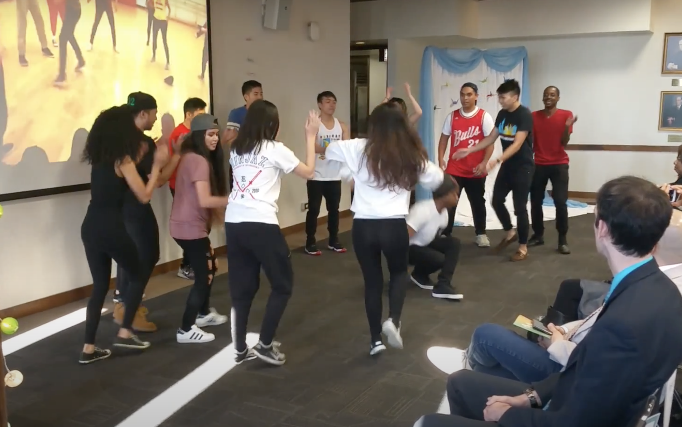 One circle of dancers of many races surrounds one mixed Black and Asian man dancing in the center