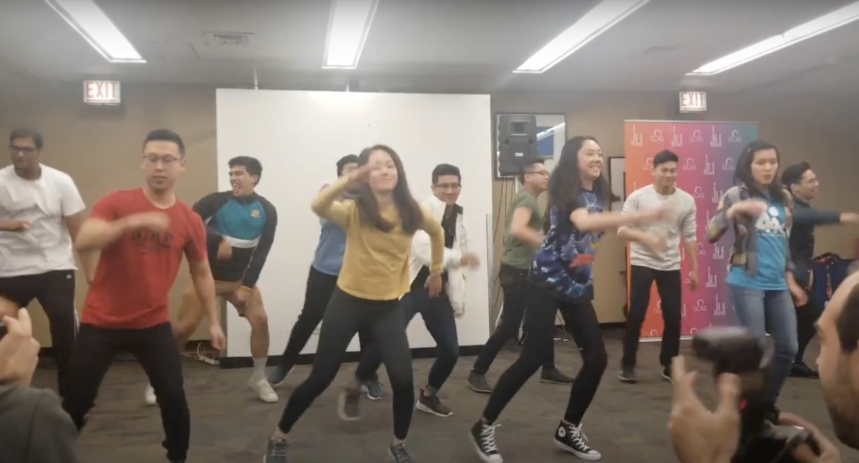 A group of many Asian American dancers performs