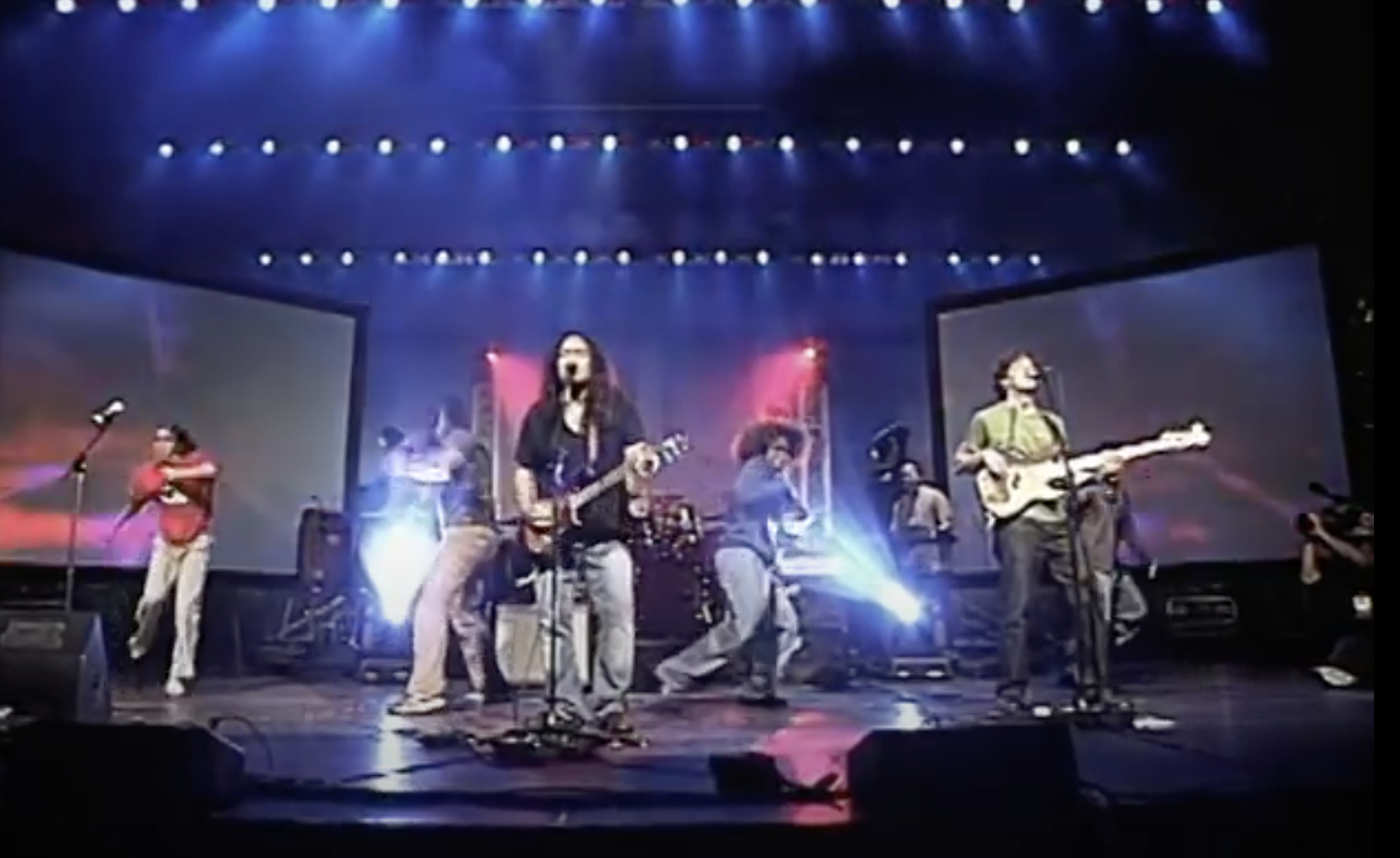 One rock artist sings and plays guitar with a band and dancers on stage