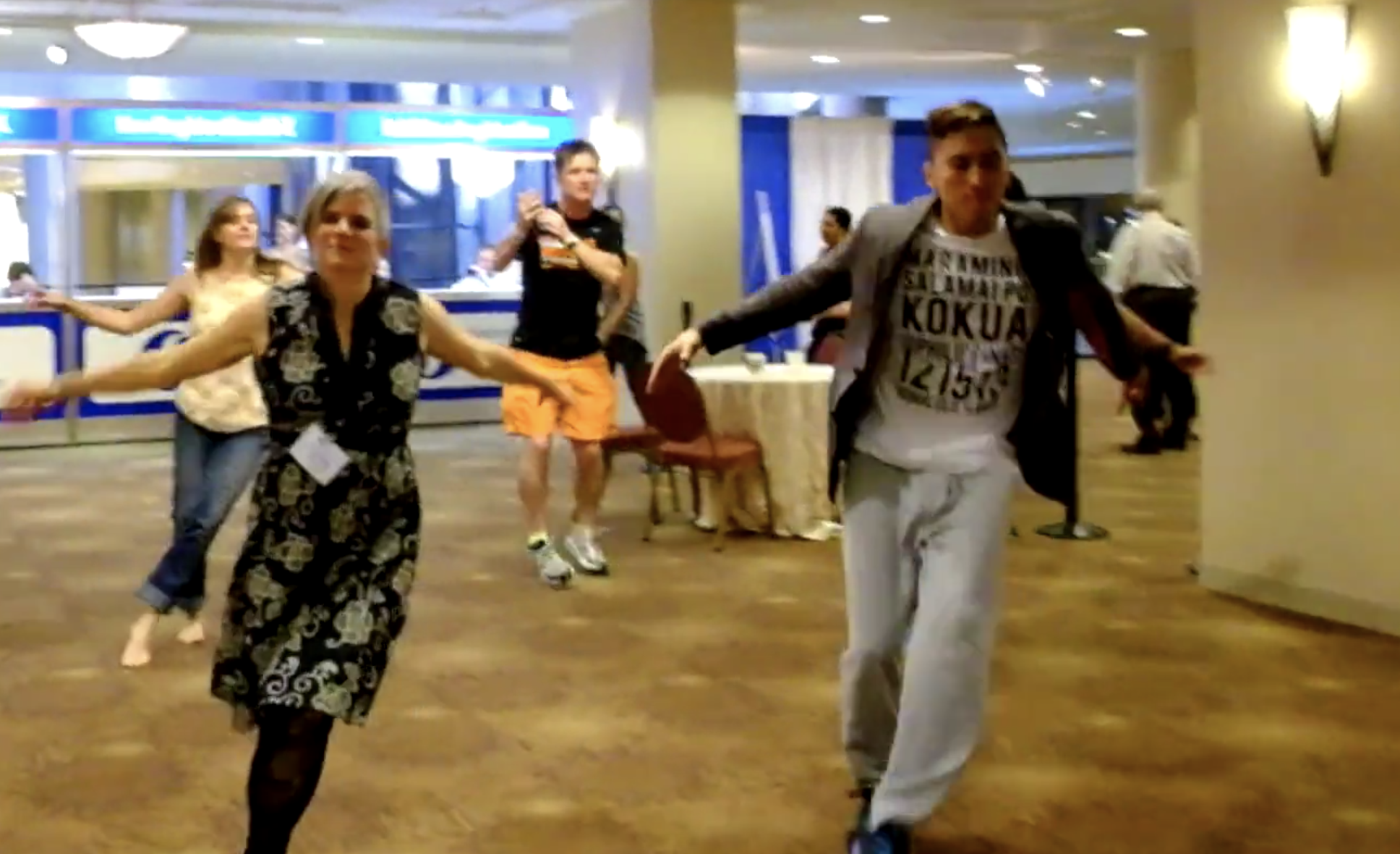 One white woman and Brown man dance in a lobby