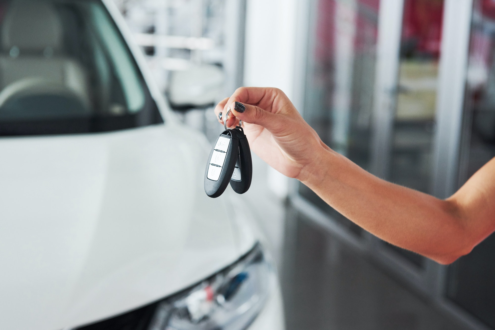 Passing car keys. Cropped closeup of a car dealer holding out car keys to the camera copyspace car