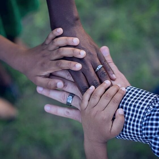 People putting their hands together to represent teamwork.