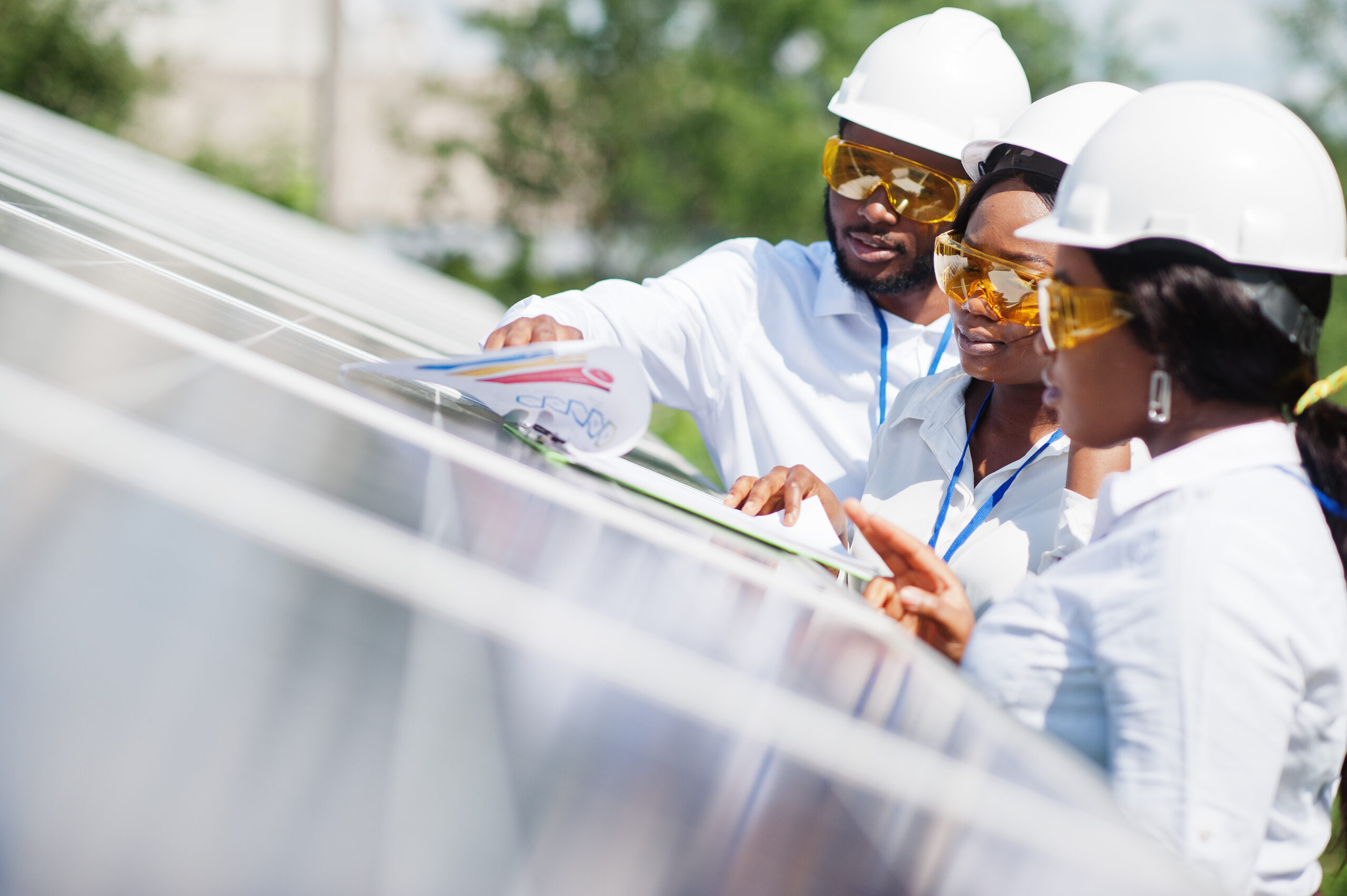 Three people wearing protective equipment standing near a solar panel and looking at some paperwork.