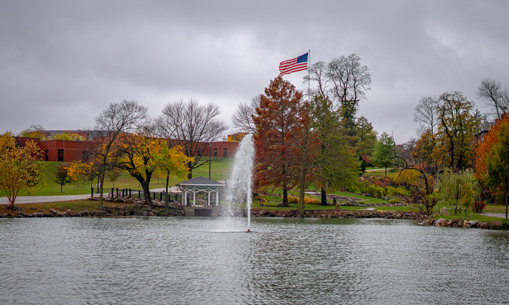 fountain in a pond with american flag in the background