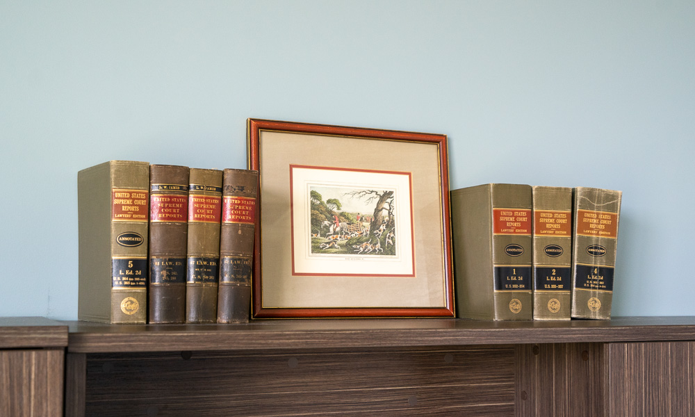 picture frame on shelf between six books