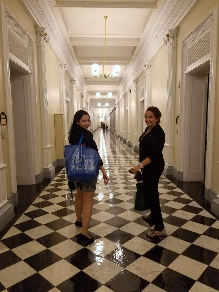 Two women walking down a checkered floor