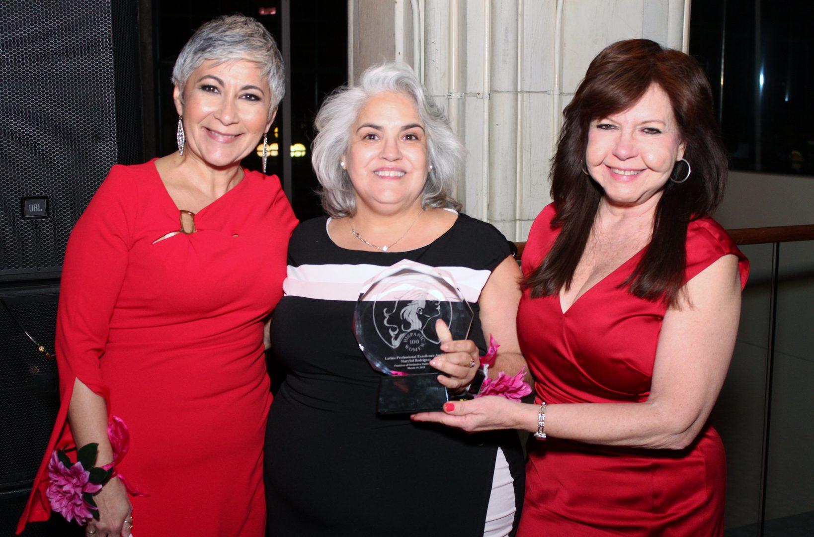 A woman holding up an award