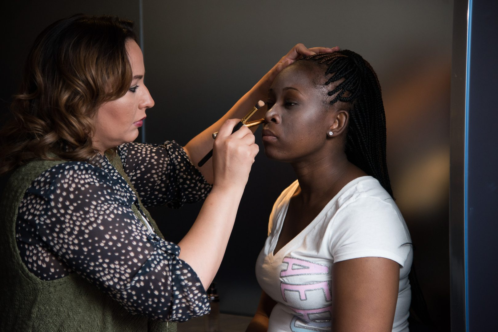 A woman putting makeup on another woman