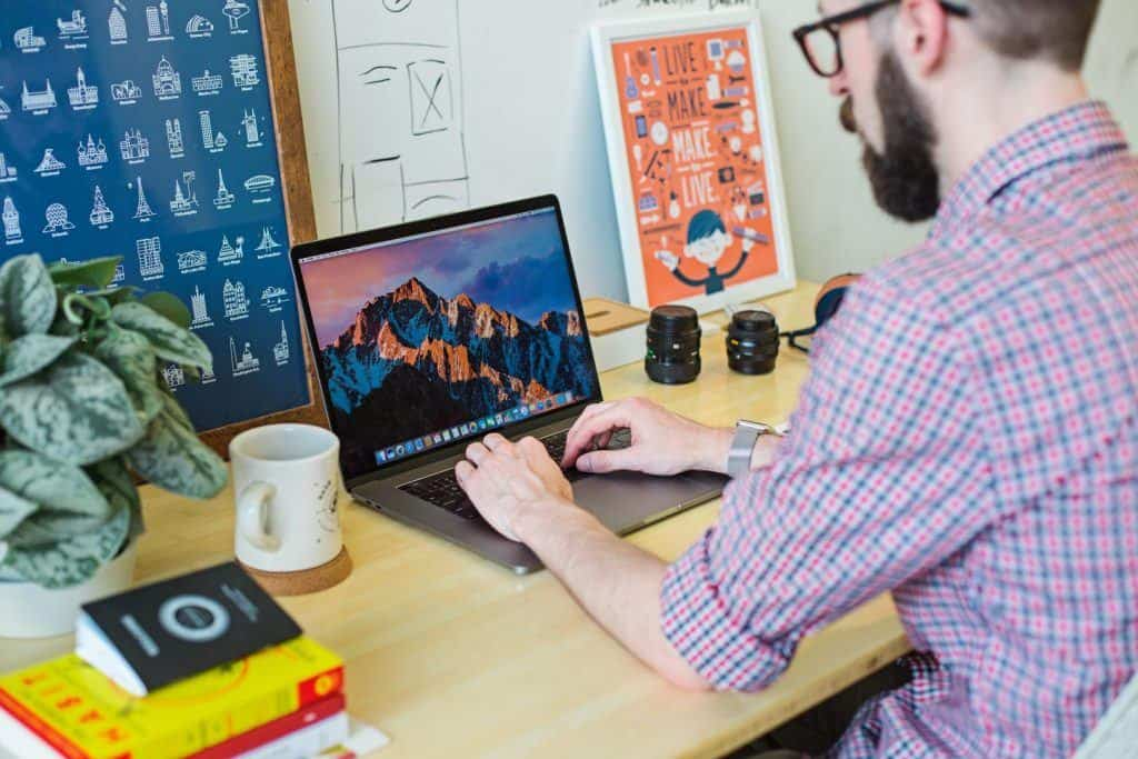 Man In A Checked Shirt Works On His Laptop