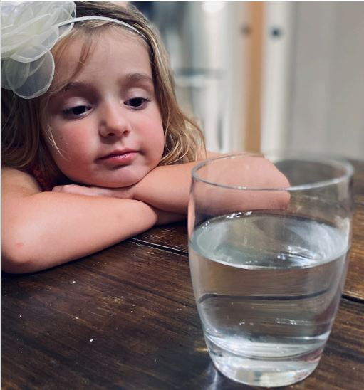Young girl looks at glass of water