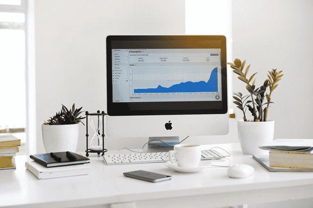 Desktop with computer, writing materials, and decorative cactus