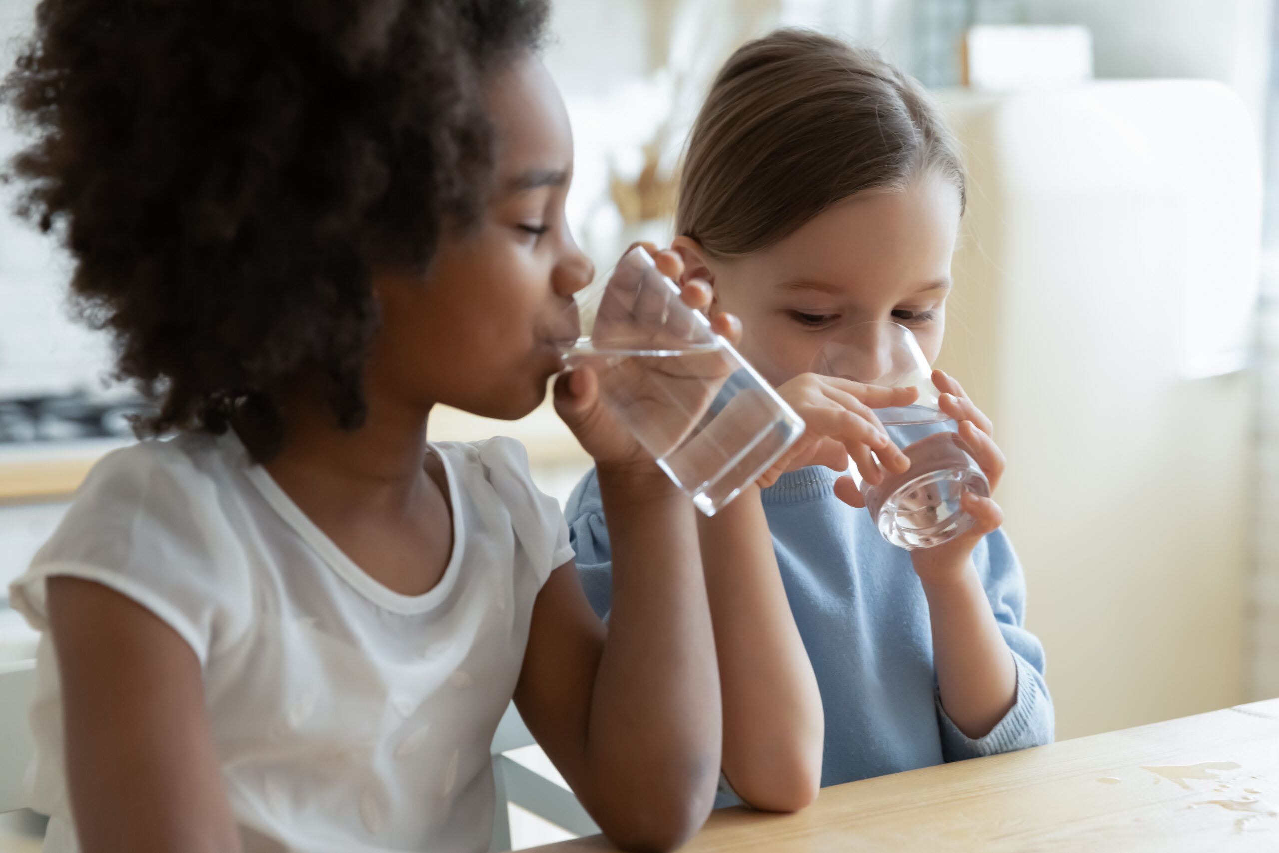 Two girls drink glasses of water