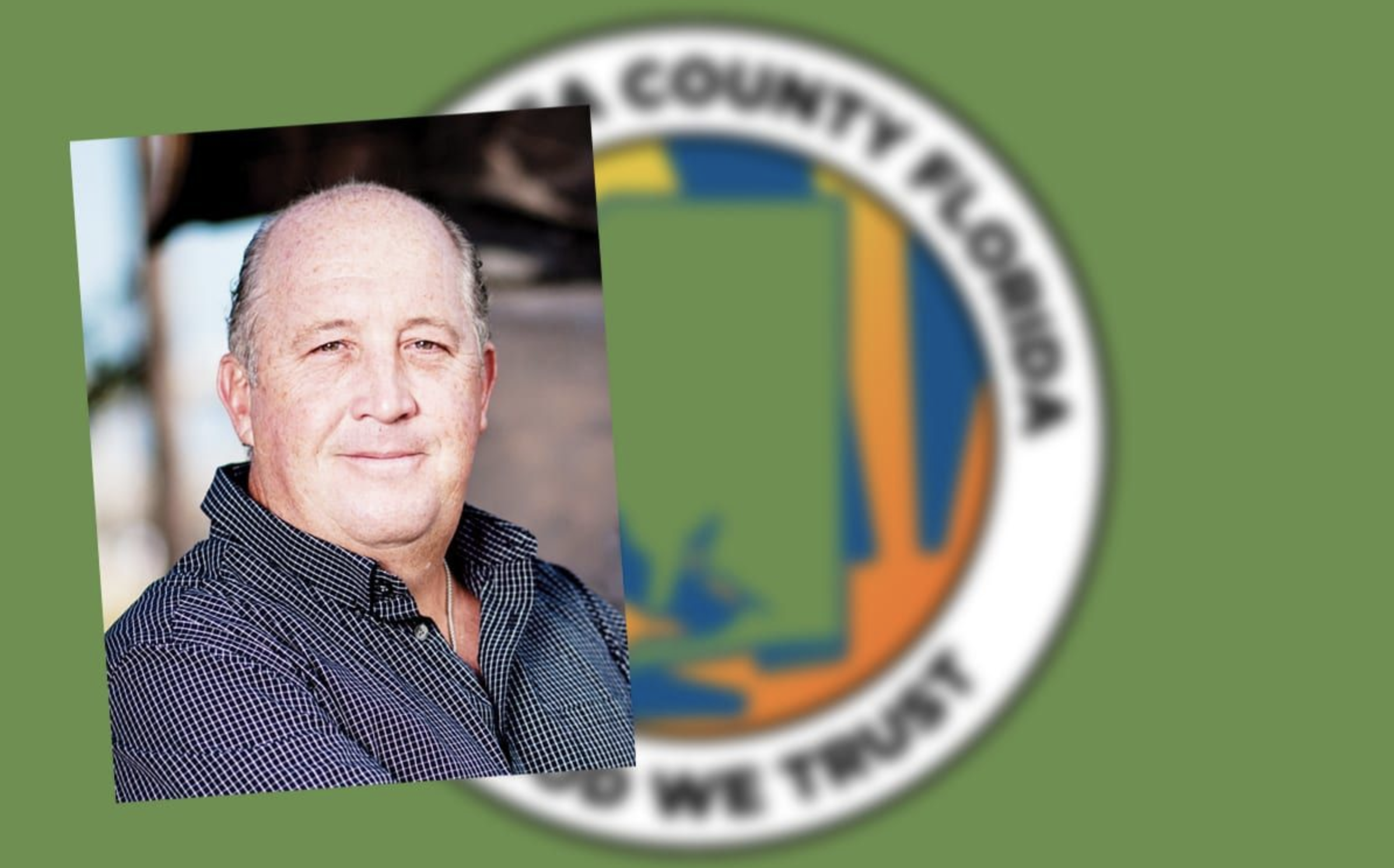 A county commissioner in front of the Santa Rosa County crest