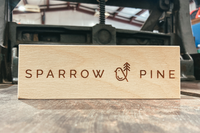 Engraved logo on a standing wooden plaque