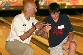 Don White assisting a student in the kneel down drill at the Dick Ritger Bowling Camp