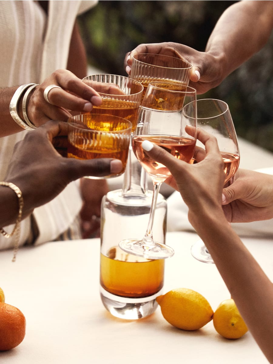 People clinking glasses of adult beverages