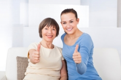 caregiver and senior showing their thumbs up