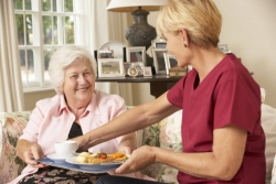 caregiver serving food to a senior