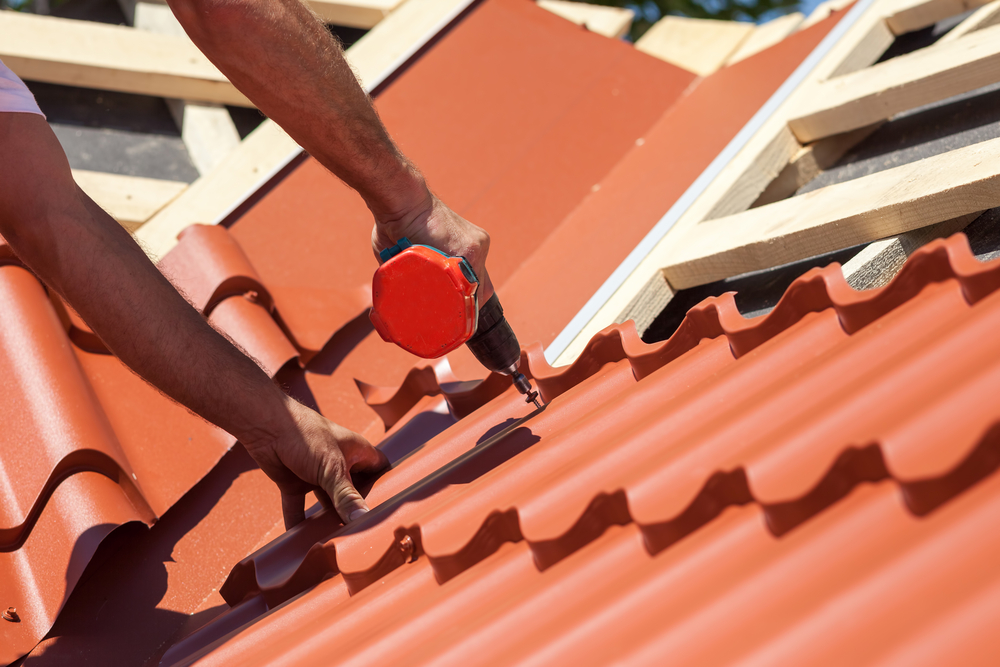 Worker installing a metal roof
