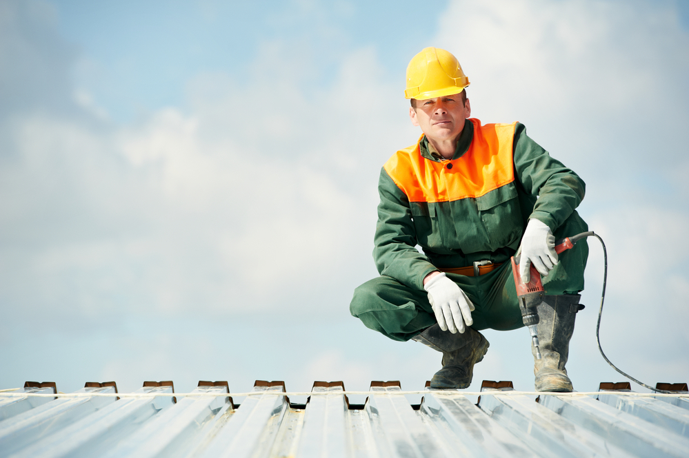 Roofer in a hard hat on top of a metal roof holding a drill