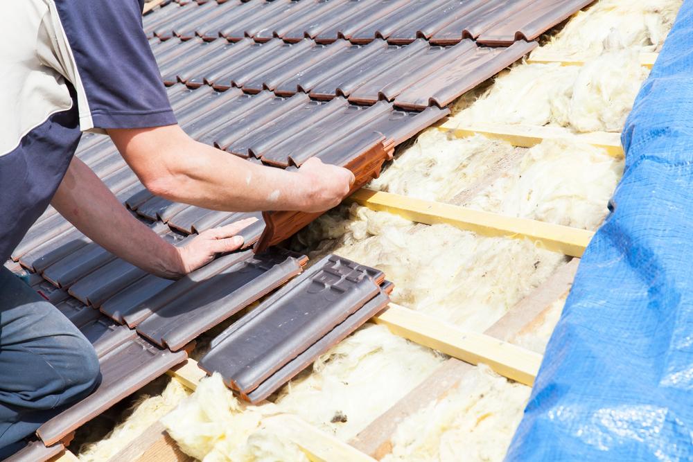 Roofer installing new roof tiles
