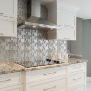 Cabinets de MDF protégés par un laque avec 20% de lustre, comptoir de granite et dosseret en mosaïque.