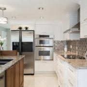 Cuisine en noyer, cabinets de MDF protégés par un laque avec 20% de lustre, comptoir de granite et dosseret en mosaïque