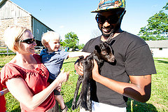 Image of child in mother's arms petting a lamb held by a loudoun county farmer